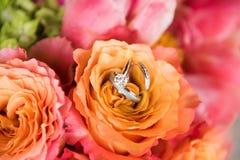 Λουλούδια με τα γαμήλια δαχτυλίδια στοκ φωτογραφία με δικαίωμα ελεύθερης χρήσης