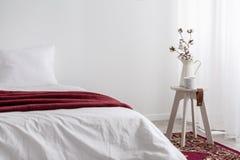 Λουλούδια στον πίνακα δίπλα στο άσπρο κρεβάτι με το κόκκινο κάλυμμα στο ελάχιστο εσωτερικό κρεβατοκάμαρων στοκ φωτογραφία με δικαίωμα ελεύθερης χρήσης