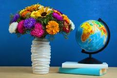 Λουλούδια, σφαίρα και βιβλία Στοκ Εικόνες