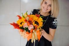 Λουλούδια φθινοπώρου στα χέρια της γυναίκας Κολοκύθα, ηλίανθοι και άλλα λουλούδια Στοκ εικόνες με δικαίωμα ελεύθερης χρήσης