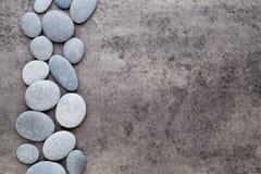 Λουλούδια SPA και πέτρα μασάζ, στο γκρίζο υπόβαθρο Στοκ Φωτογραφίες