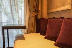Λουξ εσωτερικό κρεβατοκάμαρων του ενσωματωμένου καναπέ με το μαξιλάρι και το κινητό τραπεζάκι σαλονιού Στοκ Εικόνες