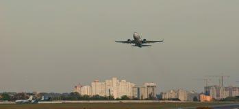Λουρίδα αεροδρομίων απογείωσης επιβατών αεροπλάνου στο υπόβαθρο της πόλης Στοκ Εικόνα