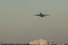 Λουρίδα αεροδρομίων απογείωσης επιβατών αεροπλάνου στο υπόβαθρο της πόλης Στοκ Εικόνες