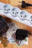 Λουρίδα ηλεκτρικής δύναμης με τα αποσυνδεμένα βουλώματα και τα χρήματα νομίσματος στιλβωτικής ουσίας, ενεργειακά κόστη Στοκ φωτογραφίες με δικαίωμα ελεύθερης χρήσης