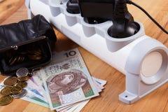 Λουρίδα ηλεκτρικής δύναμης με τα συνδεδεμένα βουλώματα και τα χρήματα νομίσματος στιλβωτικής ουσίας, ενεργειακά κόστη Στοκ Φωτογραφία
