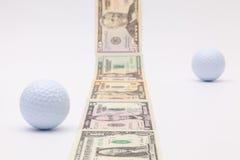 Λουρίδα των διαφορετικών τραπεζογραμματίων αμερικανικών δολαρίων και της άσπρης σφαίρας γκολφ Στοκ Φωτογραφίες