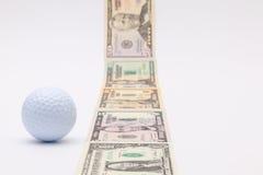 Λουρίδα των διαφορετικών τραπεζογραμματίων αμερικανικών δολαρίων και της άσπρης σφαίρας γκολφ Στοκ Εικόνες