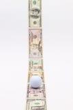 Λουρίδα των διαφορετικών τραπεζογραμματίων αμερικανικών δολαρίων και της άσπρης σφαίρας γκολφ Στοκ εικόνα με δικαίωμα ελεύθερης χρήσης