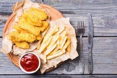 Λουρίδες και τηγανιτές πατάτες κοτόπουλου Στοκ Εικόνες