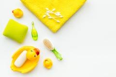Λουτρό μωρών που τίθεται με την κίτρινη λαστιχένια πάπια Σαπούνι, σφουγγάρι, βούρτσες, πετσέτα στην άσπρη τοπ άποψη υποβάθρου cop Στοκ Φωτογραφία