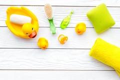 Λουτρό μωρών που τίθεται με την κίτρινη λαστιχένια πάπια Σαπούνι, σφουγγάρι, βούρτσες, πετσέτα στην άσπρη ξύλινη τοπ άποψη υποβάθ Στοκ Φωτογραφίες