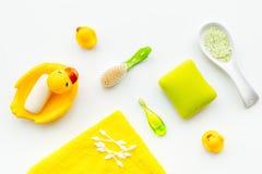 Λουτρό μωρών που τίθεται με την κίτρινη λαστιχένια πάπια Σαπούνι, σφουγγάρι, βούρτσες, πετσέτα στην άσπρη τοπ άποψη υποβάθρου Στοκ εικόνα με δικαίωμα ελεύθερης χρήσης
