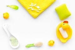 Λουτρό μωρών που τίθεται με την κίτρινη λαστιχένια πάπια Σαπούνι, σφουγγάρι, βούρτσες, πετσέτα στην άσπρη τοπ άποψη υποβάθρου cop Στοκ Εικόνα