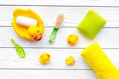 Λουτρό μωρών που τίθεται με την κίτρινη λαστιχένια πάπια Σαπούνι, σφουγγάρι, βούρτσες, πετσέτα στην άσπρη ξύλινη τοπ άποψη υποβάθ Στοκ Εικόνα