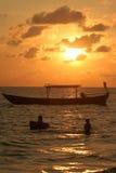 Λουόμενοι ηλιοβασιλέματος στην παραλία εύνοιας στις τυχαίες ανακαλύψεις στοκ εικόνα με δικαίωμα ελεύθερης χρήσης