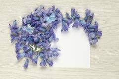 Λουλούδια άνοιξη με τις πεταλούδες και κενό φύλλο εγγράφου στον άσπρο αγροτικό πίνακα Στοκ φωτογραφία με δικαίωμα ελεύθερης χρήσης