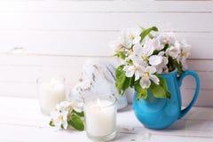 Λουλούδια δέντρων της Apple, διακοσμητικά καρδιά και κεριά στο άσπρο woode Στοκ Φωτογραφία