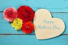 Λουλούδια δίπλα στην ξύλινη καρδιά στον ξύλινο πίνακα conce ημέρας μητέρας Στοκ Εικόνες