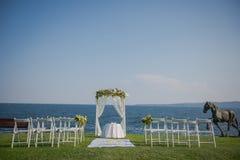 Λουλούδια γαμήλιας τελετής, αψίδα, καρέκλες με Μαύρη Θάλασσα στο υπόβαθρο Γάμος παραλιών Στοκ Εικόνες