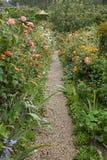 Λουλούδια εξοχικών σπιτιών διαβάσεων κήπων στα πορτοκάλια, κήπος Γαλλία Monet Στοκ Εικόνα