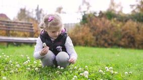 Λουλούδια επιλογής μικρών κοριτσιών στο λιβάδι απόθεμα βίντεο