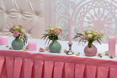 Λουλούδια και κεριά σε έναν εορταστικό πίνακα στοκ εικόνες