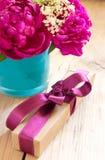Λουλούδια και παρόν κιβώτιο με την κορδέλλα στον πίνακα, δώρο γενεθλίων στοκ εικόνες