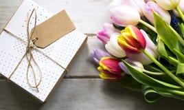 Λουλούδια και παρόν τουλιπών με τη διαστημική κενή ετικέττα σχεδίου σε ξύλινο στοκ φωτογραφία με δικαίωμα ελεύθερης χρήσης
