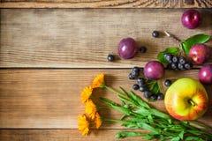 Λουλούδια και φρούτα Calendula στο ξύλινο υπόβαθρο στο αγροτικό ύφος Στοκ φωτογραφία με δικαίωμα ελεύθερης χρήσης