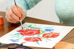 Λουλούδια παπαρουνών ζωγραφικής γυναικών Στοκ εικόνα με δικαίωμα ελεύθερης χρήσης
