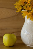 Λουλούδια σε ένα κεραμικά βάζο και ένα μήλο Στοκ Φωτογραφία