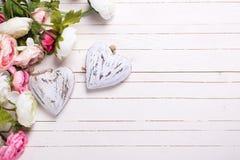 Λουλούδια στα ρόδινα χρώματα και διακοσμητικές καρδιές στο άσπρο ξύλινο BA Στοκ Εικόνες