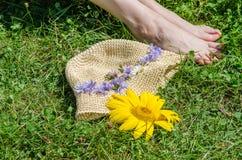 Λουλούδια στο ανοικτό κίτρινο καπέλο εγγράφου και ένα ζευγάρι των ποδιών Στοκ φωτογραφία με δικαίωμα ελεύθερης χρήσης