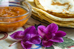 Λουλούδια στο πρώτο πλάνο και τηγανίτες με τη μαρμελάδα Στοκ φωτογραφία με δικαίωμα ελεύθερης χρήσης