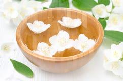Λουλούδια της Jasmine σε ένα ξύλινο κύπελλο για τη SPA και aromatherapy Στοκ Φωτογραφία