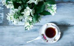 Λουλούδια της Jasmine σε ένα δοχείο και ένα φλυτζάνι του τσαγιού, αγροτικά Στοκ Φωτογραφία