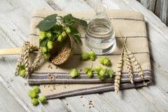 Λουλούδια λυκίσκου, αυτιά σίτου και σπόροι, νερό συστατικά για την παρασκευή της μπύρας στον ξύλινο πίνακα Στοκ Φωτογραφία