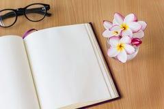 Λουλούδια Plumeria ή frangipani στο γυαλί με το κενό βιβλίο σημειώσεων και Στοκ Εικόνες