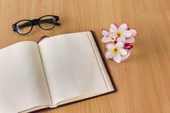 Λουλούδια Plumeria ή frangipani στο γυαλί με το κενό βιβλίο σημειώσεων και Στοκ φωτογραφία με δικαίωμα ελεύθερης χρήσης