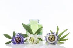 Λουλούδι πάθους με το aromatherapy μπουκάλι γυαλιού ουσιαστικού πετρελαίου μπλε και καφετί Στοκ Εικόνες