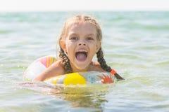 Λούσιμο κοριτσιών εξάχρονων παιδιών στη θάλασσα με το στόμα του ανοικτό στην ευχαρίστηση στοκ εικόνα