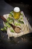 Λυκίσκοι και σπόρων και ακίδων βύνης σύνολο κανατών με την μπύρα στην πετσέτα υφασμάτων Στοκ φωτογραφία με δικαίωμα ελεύθερης χρήσης