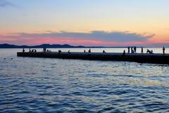 Λυκόφως στην ακτή με τους ανθρώπους στην αποβάθρα στοκ εικόνες