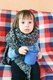 Λυπημένα ανεπαρκή 2 έτη παιδιών στο θερμό μάλλινο μαντίλι με το φλυτζάνι του τσαγιού Στοκ Φωτογραφία
