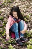 Λυπημένα Primroses κοριτσιών που κάθονται τα επίγεια ακουστικά υπαίθρια Στοκ Φωτογραφία