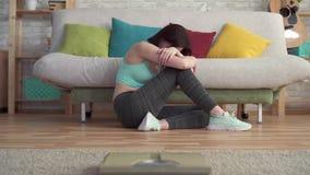Λυπημένη απογοητευμένη νέα φίλαθλη γυναίκα που φωνάζει στο πάτωμα που εξετάζει τις κλίμακες απόθεμα βίντεο