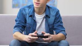 Λυπημένη απώλεια εφήβων στο τηλεοπτικό παιχνίδι, καναπές που χαλαρώνει, ανταγωνιστικό τυχερό παιχνίδι απόθεμα βίντεο