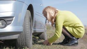 Λυπημένη γοητευτική νέα γυναίκα που ανυψώνει το σπασμένο αυτοκίνητο με τη βίδα γρύλων στον αγροτικό δρόμο 4K απόθεμα βίντεο