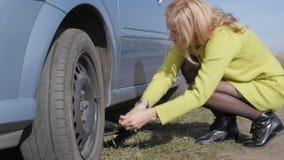 Λυπημένη γοητευτική νέα γυναίκα που ανυψώνει το σπασμένο αυτοκίνητο με τη βίδα γρύλων στον αγροτικό δρόμο κίνηση αργή απόθεμα βίντεο